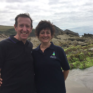 Alison Harper, business owner with her husband Karl standing on the beach with rocks behind in Cornwall