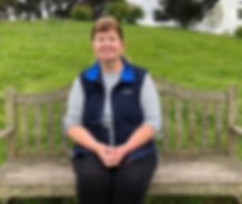 A female pet sitter, living in Dorset specialising cats sitting on a wooden bench wearing a navy body warmer with a green slope and trees behind