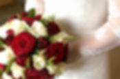 Rose wedding bouquet of wine and cream roses and a bride wearing a lace wedding dress