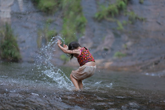 Playing in a waterfall near camp