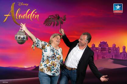 Man en vrouwen poseren voor de green screen photobooth van Aladdin in Kinepolis Brussel