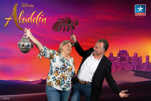 Man en vrouwen poseren voor de green screen photobooth van Aladdin in Kinepolis Brussel