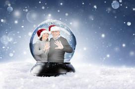 Man en vrouw poseren in een sneeuwkubus tijdens Kerstmis