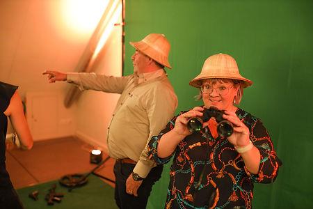 Klanten photobooth Limburg - Man en vrouw met verrekijker poseert voor de green screen photobooth