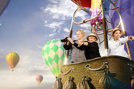 Twee vrouwen en een man poseren voor de green screen photoobooth en zitten in een luchtballon