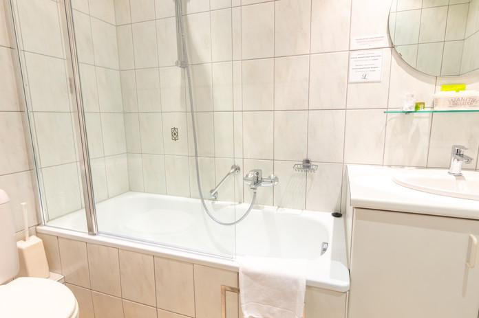 Badkamer met bad en douche bij Hostellerie Beau Site