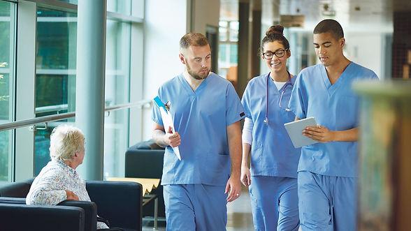 Dokters en twee verplegers dragen gepaste bedrijfskleding in een ziekenhuis