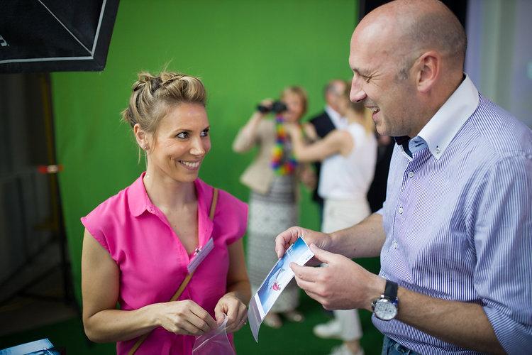 Man en vrouw lachen met de uitgeprinte foto van een green screen photobooth