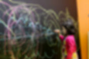 child writing on a chalkboard wall accent paint church toddler room modern church interior design san antonio, texas