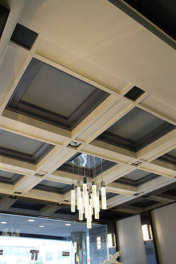 Modern coffered ceiling with contemporary chandelier in lobby of historic building