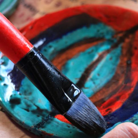 student applying a glaze