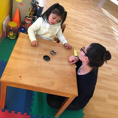 Ninos Felices - Girl sat at small table.