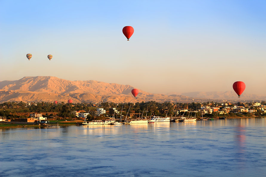 Hot air balloons floating over the Nile River in Luxor at sunrise.jpg
