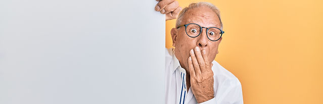Elderly man wearing glasses with his hand to his mouth as if surprised - yellow background