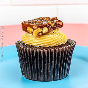 Cupcake de chocolate com recheio e cobertura de brigadeiro de paçoca e no topo caramelo de amendoim com flor de salespecial da Alegra e da Chef Mariana Vincenzi