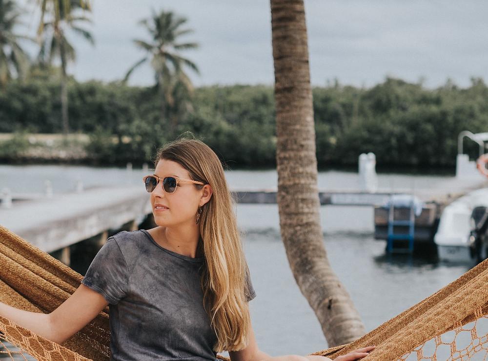Holly Canon Travel and Lifestyle Blog Grand Cayman 2017 2018 Camana Bay Bia Alvarez Photography Island Style Island Life Cayman Islands Photographer Yellow Palm Trees Grey Dress Sunglasses Blond Hair Smile Sunshine