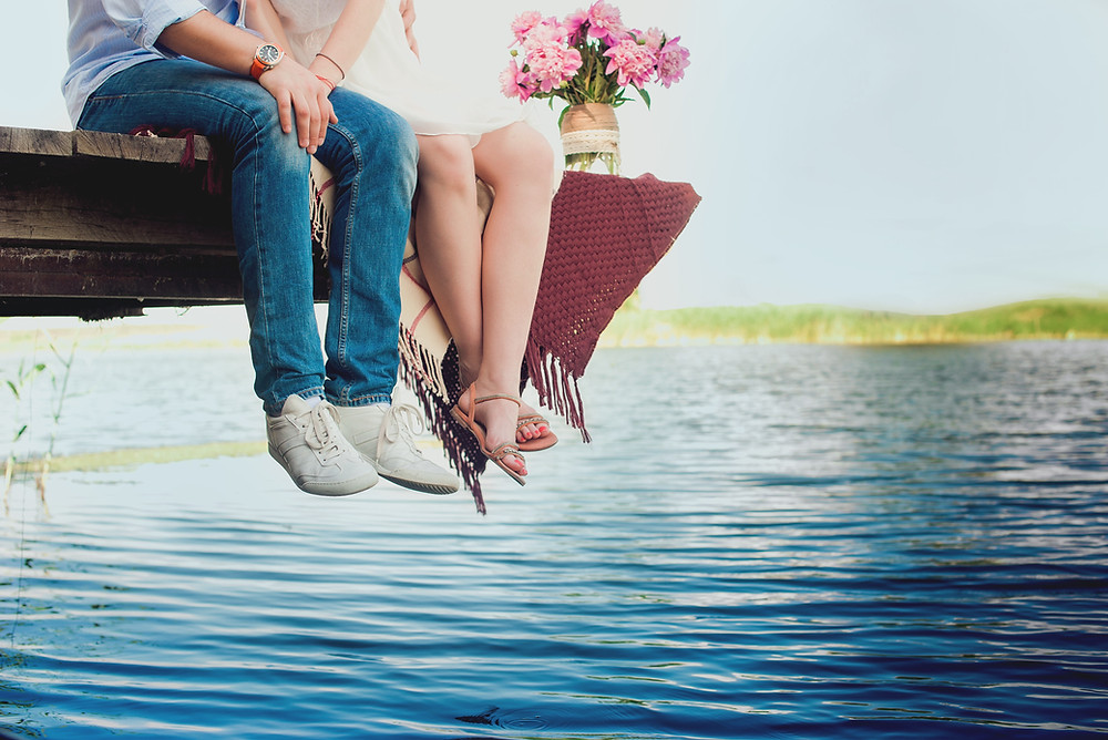 Couple in love sitting on the dock over the lake