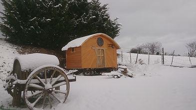 roulotte chapelle en bois sous la neige