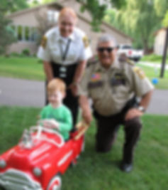 Photo of sheriff's deputy and volunteer with a child at a community event