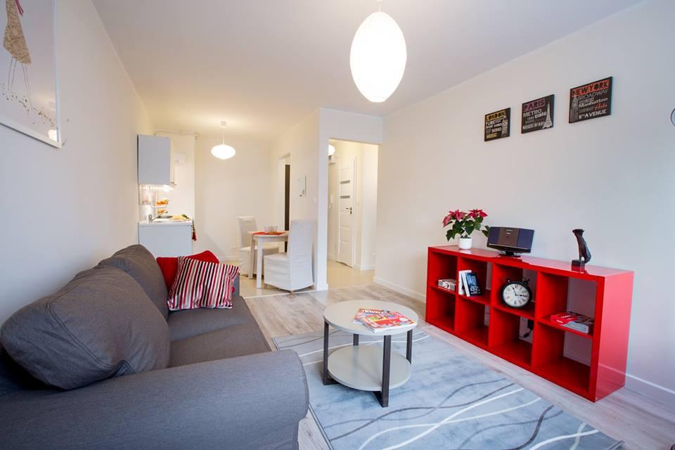 Przygotowane przez nas mieszkanie na wynajem, neutralne wnętrze z dodatkami w kolorze czerwieni.