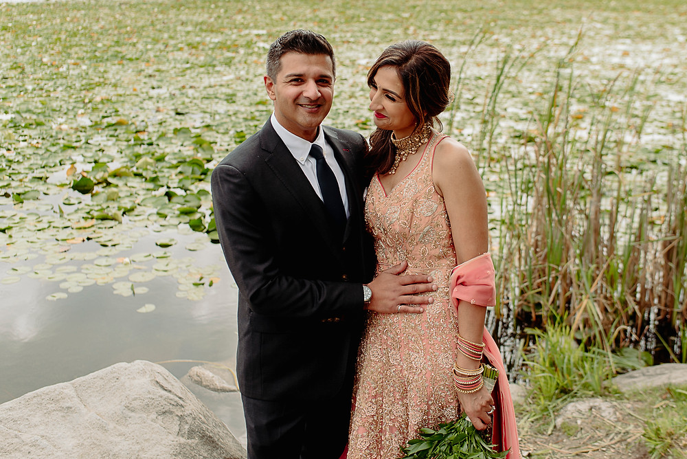 bride looks lovingly at groom beside lake with lillypads