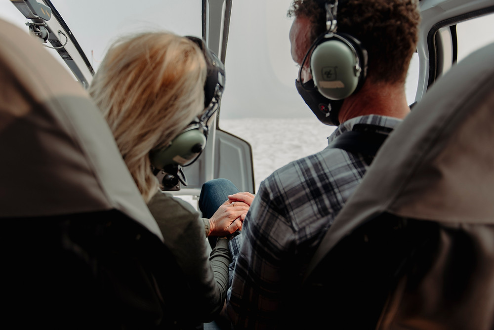 Couple holds hands showing off engagement ring while flying back down to Blackcomb Helicopters base in Whistler valley