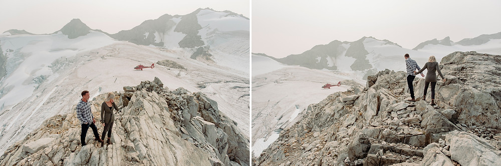 Newly engaged couple explores Rainbow Glacier rocky mountain top with helicopter in the background after getting engaged