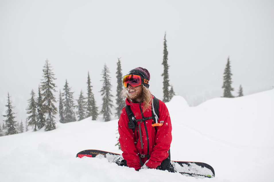 happy-snowboarder-sits-in-snow-after-dropping-cliff-in-powder-callaghan-valley-journeyman-lodge