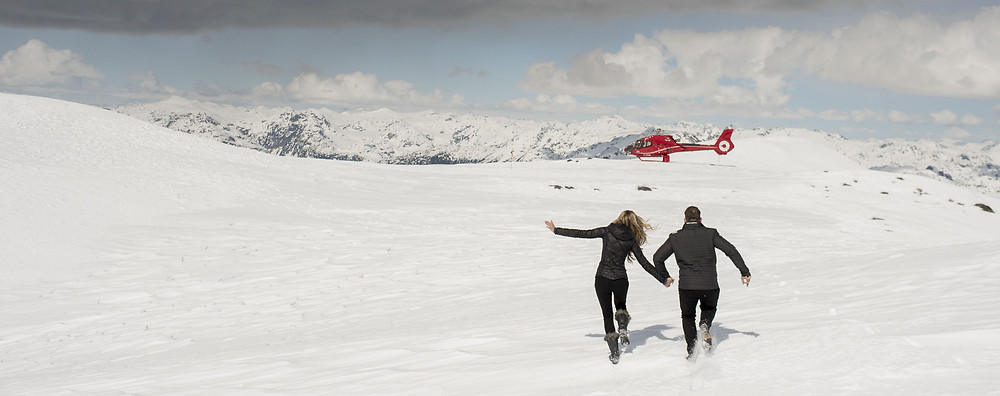 Newly engaged couple playfully runs back toward Whistler helicopter after getting engaged on Rainbow Glacier