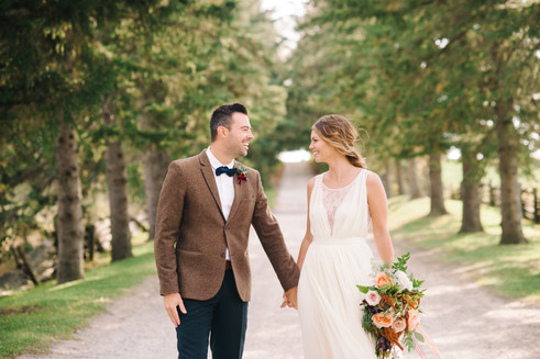 couple-smiles-toward-each-other-tree-lined-road-pemberton-british-columbia