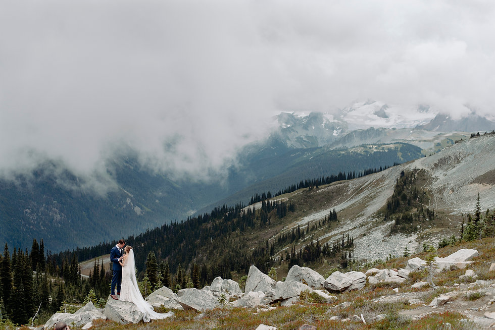 wedding couple standing on boulder at the top of whistler mountain