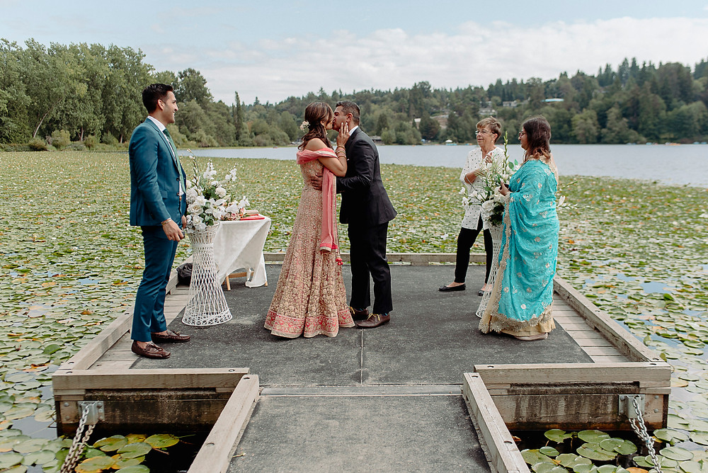 bride groom have first kiss on dock lakeside ceremony vancouver