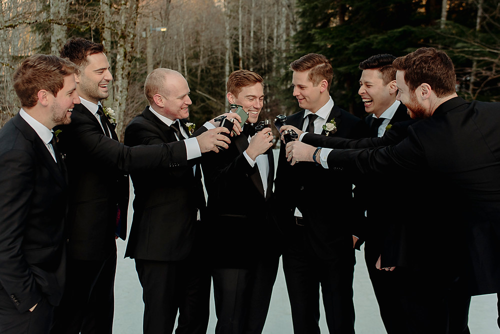 Groomsmen toasting groom with hip flask of whiskey during Whistler winter wedding