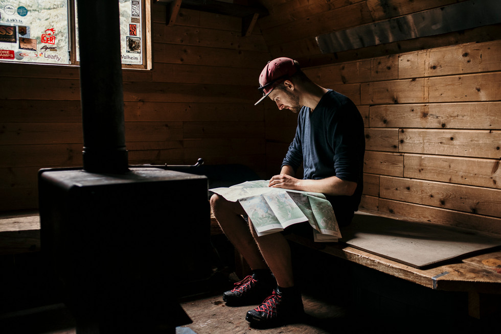 man-studies-backcountry-map-in-cabin-pemberton-british-columbia
