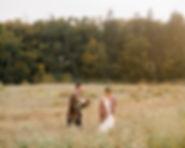 Elopement couple walk through Pemberton field after outdoor elopement ceremony