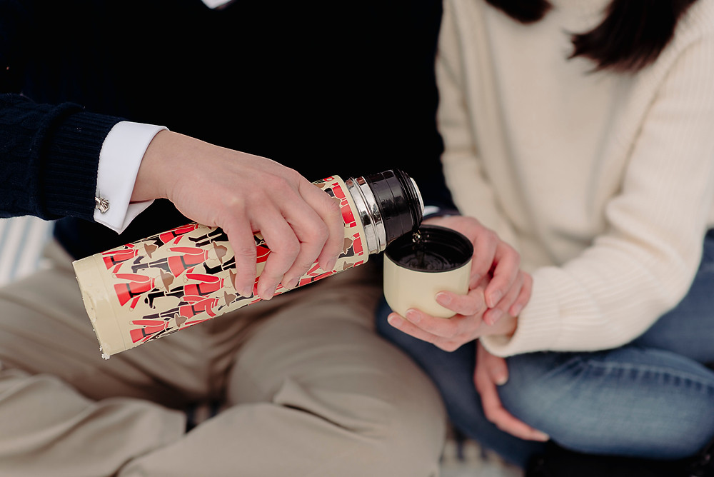 Couple shares thermos of hot tea during winter engagement photography session in Whistler