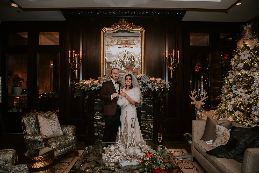 Bride groom pose in front of grand fireplace with champagne glasses in Wedgewood Hotel downtown Vancouver
