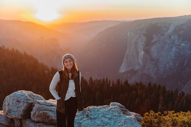 Adventure elopement photographer stands in front of sunset overlooking Yosemite Valley in California