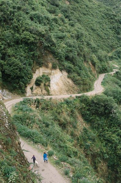 mother-son-walk-along-dirt-road-peru