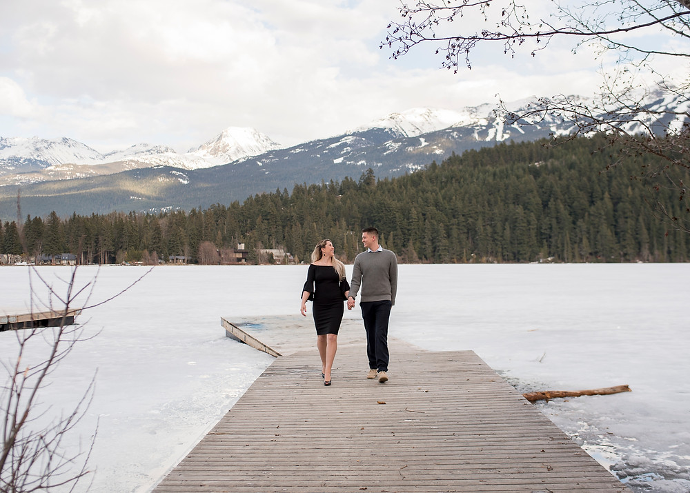 Happy couple walk back toward camera after Whistler proposal at Rainbow Park
