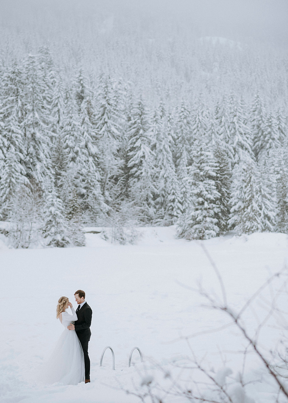 Winter elopement at Nita Lake Lodge in Whistler bride groom have tearful first look on dock by frozen lake