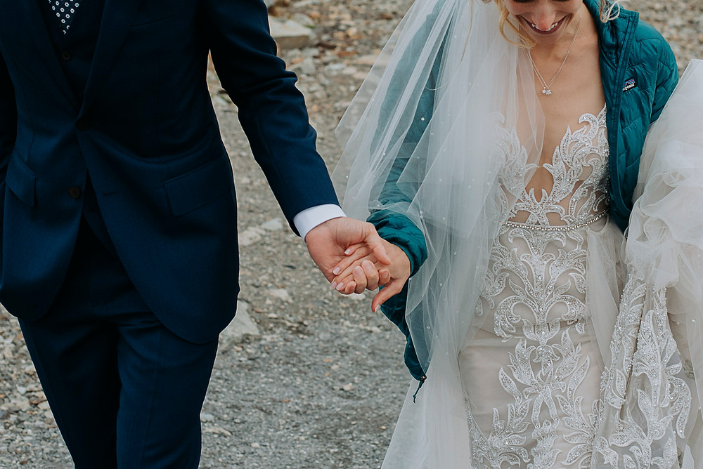 Bride wears blue Patagonia puffy jacket at top of Whistler mountain to stay warm in between Whistler wedding photos