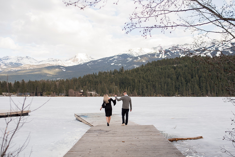 Man woman walk down dock on frozen lake overlooked by snowy Whistler mountains