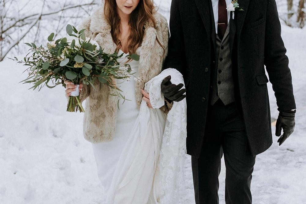 Bride groom wear warm fur jackets during winter elopement photography at Nita Lake Lodge Whistler