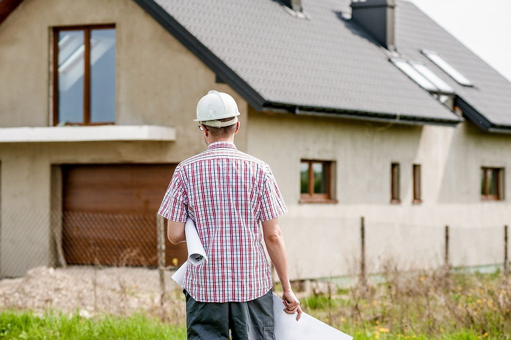 Builder overlooking a house