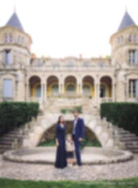 Mariés avec leur enfants devant un château pour un mariage original. La mariée à une robe bleu en dentelle, le marié à un costume bleu marine.