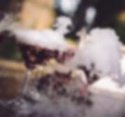 Bar à cocktail pour un mariage rock et original. Il y a des cocktails fumants sur une table en bois