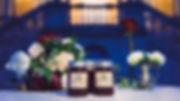 Cadeaux d'invités pour un mariage original. On voit des pots de confiture avec le logo des mariés. Derrière il y a des compositions florales originales avec des roses rouges et des pivoines blanches
