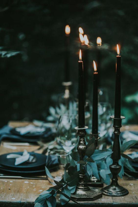 Décoration de table de mariage épurée dans un style rock et chic. Chandeliers et bougies noires avec eucalyptus. Wedding planner atypique pour mariages insolites.