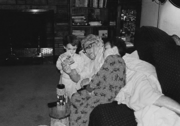 Mom reading to Chet and Katherine lying on her right side on the left side of the sofa 1993-bw